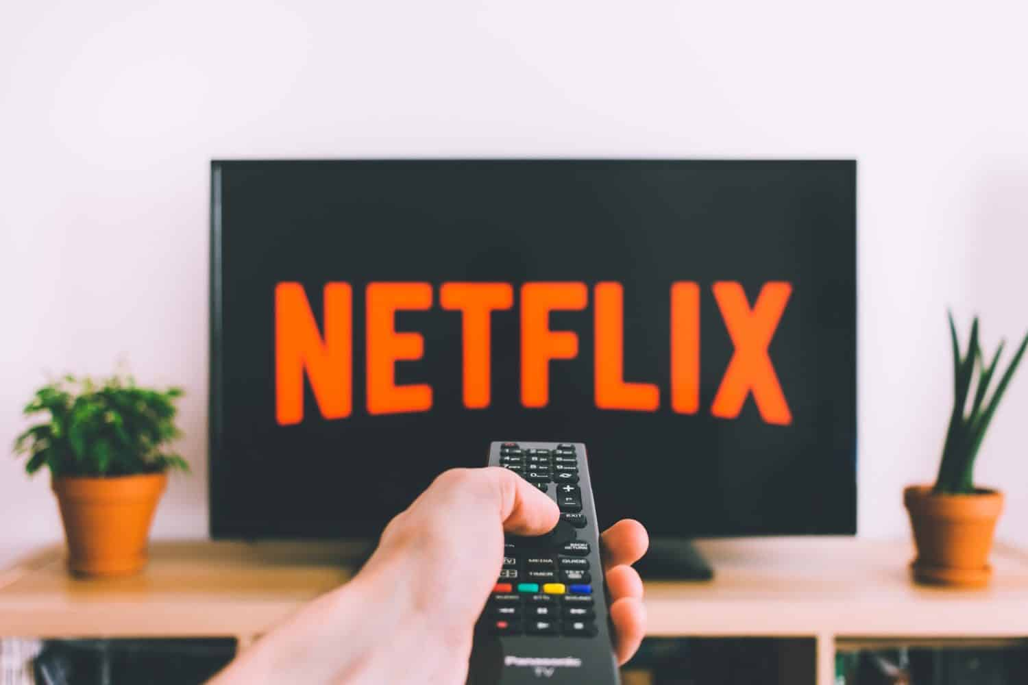 Person holding TV remote pointed at TV displaying the Netflix logo